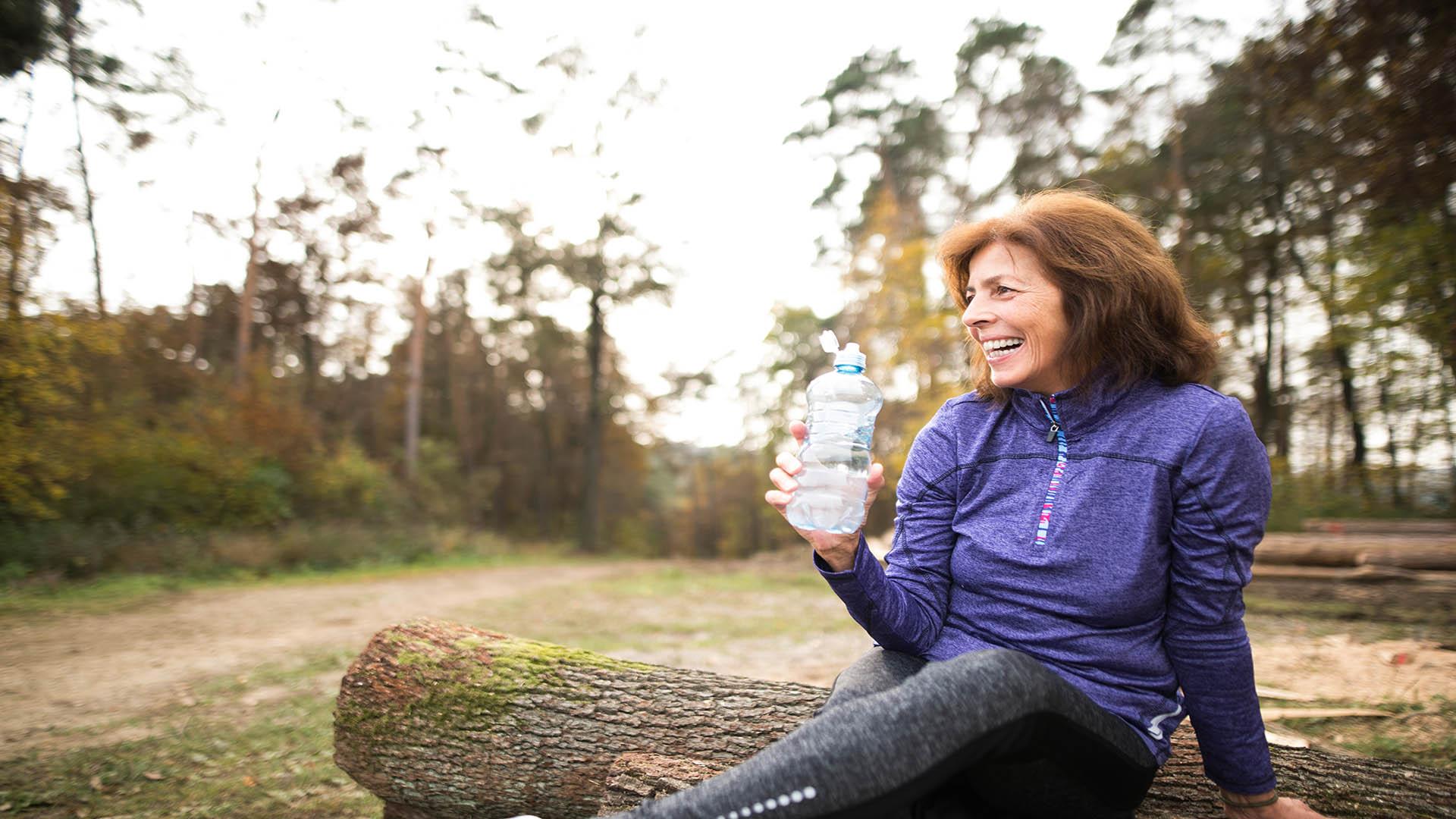 Senior Runner Sitting On Wooden Logs Resting Drinking Water